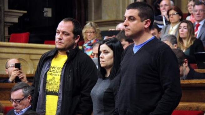 Los diputados de la CUP David Fernández, Isabel Vallet y Quim Arrufat escuchan, de pie, la respuesta del consejero de Interior, Ramon Espadaler, antes de abandonar el hemiciclo en protesta por la condena de ocho indignados por el asedio al Parlament.