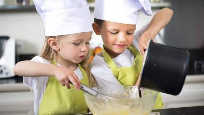 Dos niños en la cocina, preparando una receta.