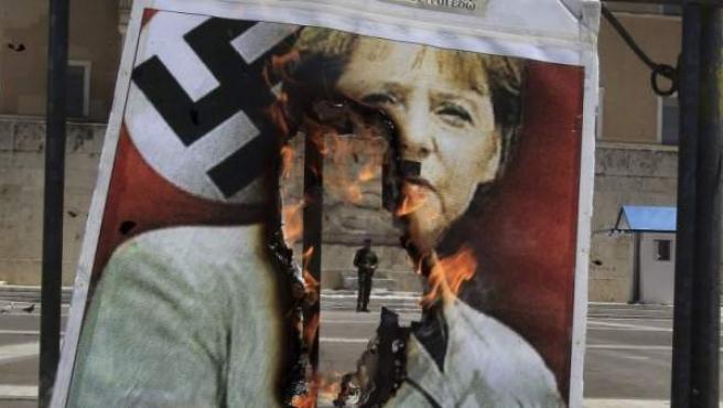 Vista de un cartel en llamas con una imagen de la canciller alemana, Angela Merkel, vestida con un uniforme nazi, frente al Parlamento griego, en Atenas, Grecia.