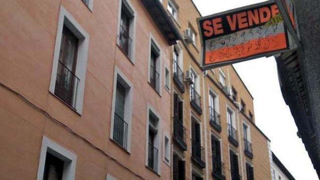 El cartel de Se Vende en la fachada de un edificio.