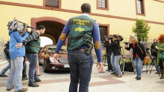 Agentes de la Unidad Central Operativa (UCO) de la Guardia Civil protegen la salida de un vehículo en la sede de la Diputación Provincial de Sevilla