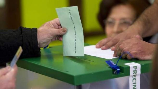 Un ciudadano introduce su voto en una de las urnas instaladas en un colegio electoral de Córdoba de cara a las elecciones andaluzas.