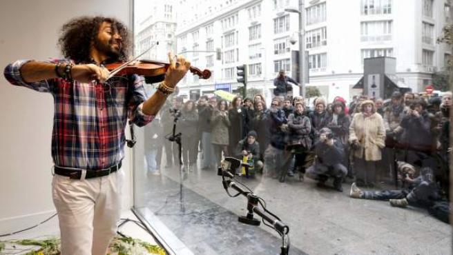El violinista armenio Ara Malikian ofrece un concierto dentro del escaparate de una tienda de ropa en la Gran Vía madrileña, con motivo de la campaña Gente con talento.