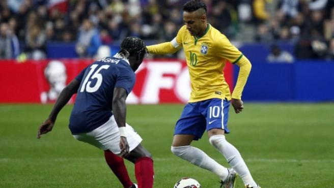 El jugador de Brasil Neymar (d) disputa el balón con Bacary Sagna (i) de Francia, durante el amistoso internacional disputado en París el 26 de marzo de 2015.