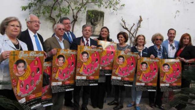 Fuentes y Reina (centro), con miembros de la AECC mostrando el cartel de la gala