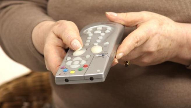 Una mujer manipula su mando a distancia.