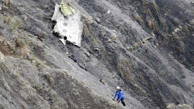 Un miembro de los servicios de rescate camina al lado del mayor un tramo de fuselaje del avión siniestrado
