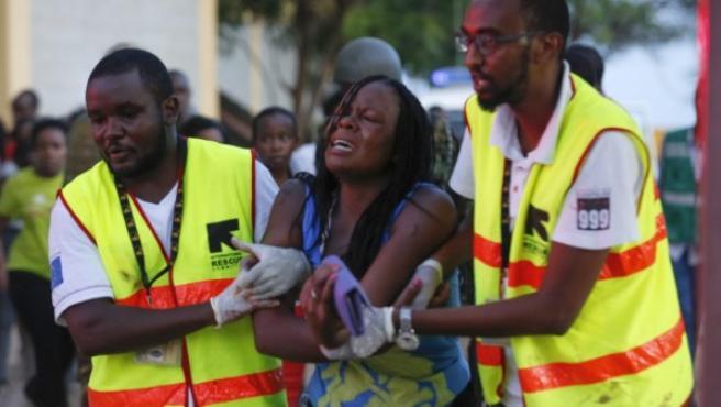 Dos sanitarios ayudan a una mujer que ha escapado de la Universidad de Garissa, en el este de Kenia, en un ataque del grupo islamista Al Shabab.