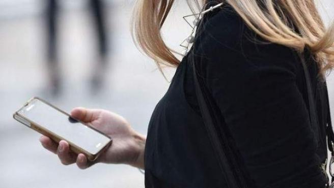 Una mujer usa su 'smartphone' mientras pasea por la calle.