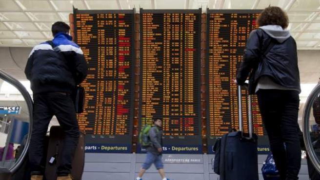 Dos viajeros comprueban la información de los vuelos en las pantallas del aeropuerto Charles de Gaulle, en Roissy (Francia).