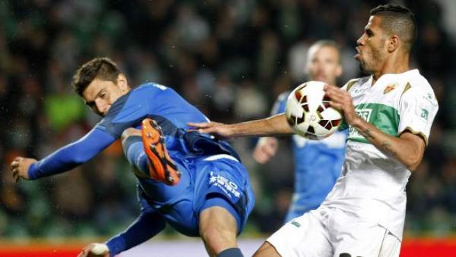El defensa uruguayo del Getafe, Emiliano Daniel Velázquez (i), despeja un balón ante el delantero brasileño del Elche, Jonathas.