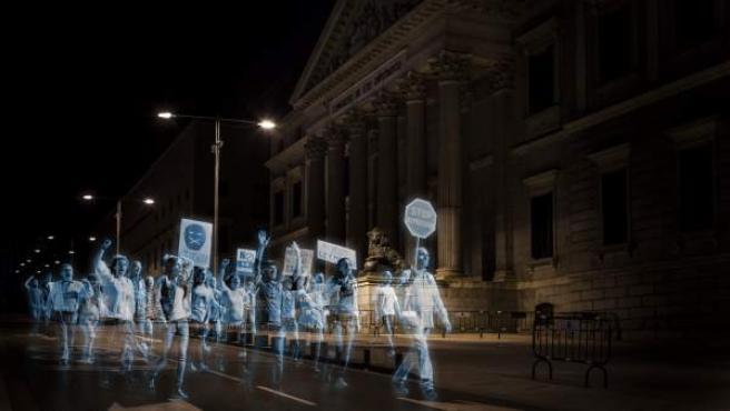 """Manifestación de hologramas ante la plaza de las Cortes donde sus participantes eran personas de todo el mundo que se """"escanearon"""" y dejaron sus mensajes a través de la web hologramasporlalibertad.org, apoyando la acción."""