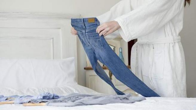 Una mujer mira unos pantalones ajustados.
