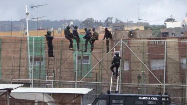 Una veintena de inmigrantes subidos a la valla de Melilla, en una imagen de archivo.