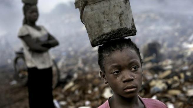 Fati, de ocho años, busca residuos tóxicos en un vertedero de chatarra electrónica en Acra (Ghana) a cambio de unos céntimos al día