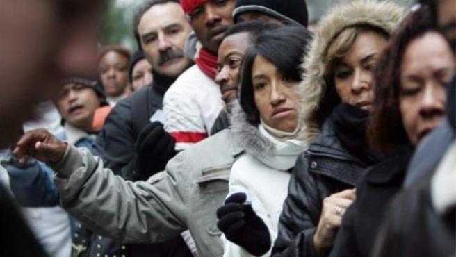 Personas haciendo cola en Madrid, entre ellos trabajadores extranjeros.