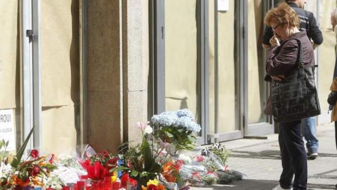 Una mujer observa las flores depositadas ante la escuela Joan Fuster de Barcelona por la muerte, ayer, de un profesor atacado por un alumno de 13 años y por el que la comunidad educativa de Cataluña protagonizará hoy concentraciones silenciosas en todos los centros escolares.