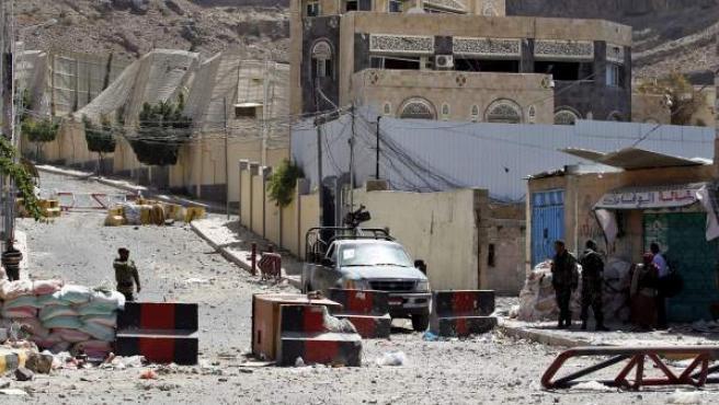 Soldados yemeníes leales al expresidente Ali Abdalá Saleh vigilan en un punto de control a las puertas del canal privado de televisión de Saleh, recientemente atacado por la coalición liderada por Arabia Saudí, en Saná, Yemen.