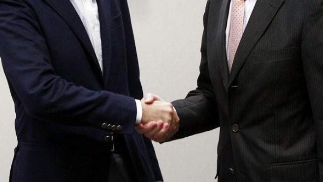 Dos trabajadores estrechándose la mano