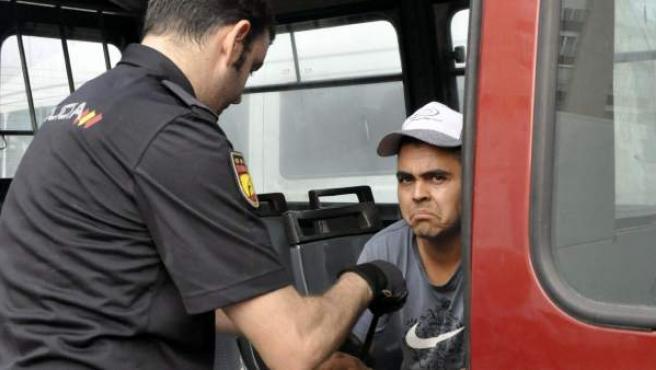 Un agente de Policía junto a un inmigrante detenido en un control contra el acceso ilegal a la Península de inmigrantes escondidos en las atracciones de la feria de Ceuta.