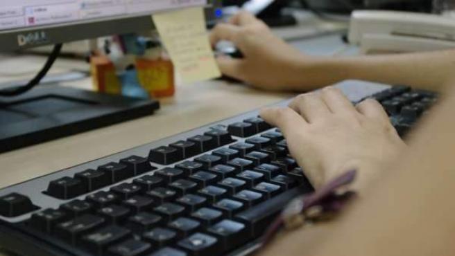 Una mujer busca empleo desde su ordenador.