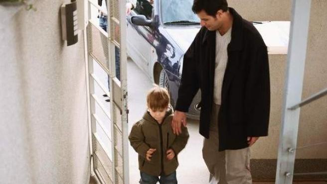 Un padre entra en casa con su hijo.