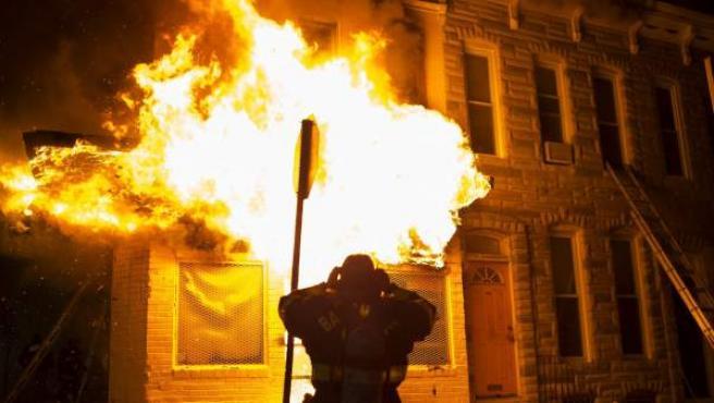 Bomberos acuden a extinguir las llamas en un edificio durante los disturbios provocados durante una protesta contra la muerte de Freddie Gray en Baltimore (Estados Unidos). Incendios, saqueos de tiendas y altercados con la Policía sumieron hoy a Baltimore en el caos.