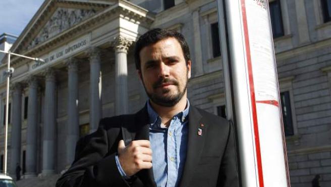 Alberto Garzón, líder de Izquierda Unida, en una parada de autobús junto al Congreso de los Diputados.