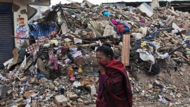 Una mujer camina delante de un edificio en ruinas tras el terremoto en Katmandú, Nepal.
