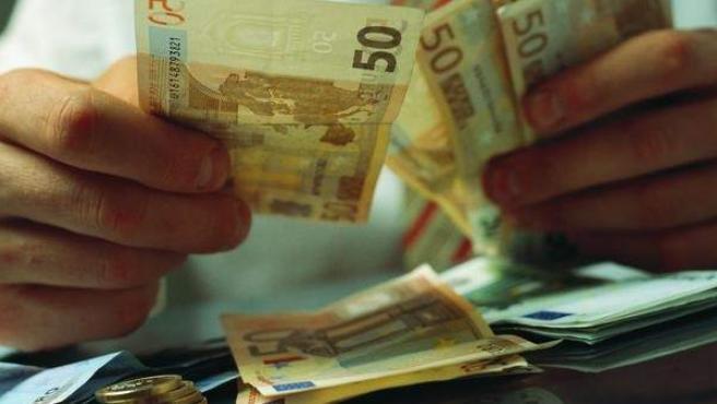 Un hombre recuenta billetes y monedas de euro.