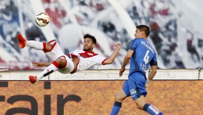 El delantero del Rayo Vallecano, Alberto Bueno (i), intenta una chilena ante el defensa uruguayo del Getafe, Emiliano Velázquez (d), del Getafe, durante el encuentro de la 36º jornada de Liga de Primera.