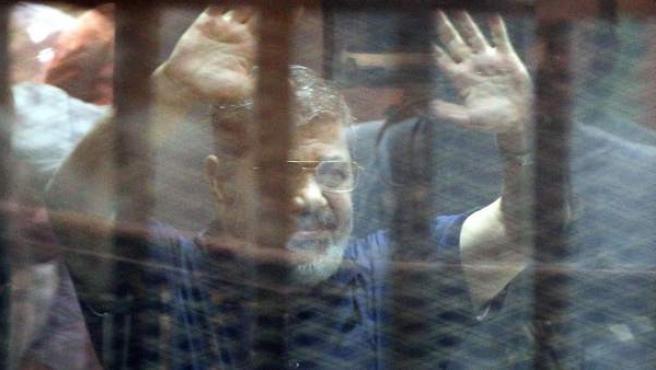 Imagen del depuesto presidente egipcio Mohamed Morsi, gesticulando desde una celda en la sala del tribunal donde fue juzgado y sentenciado a muerte en El Cairo, Egipto.