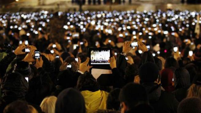 Multitud de personas toman fotos con sus dispositivos móviles.