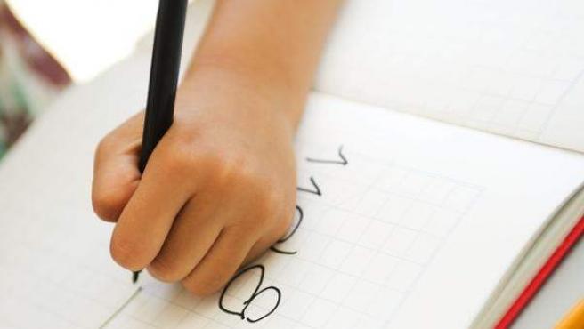 Un niño escribiendo en su pupitre.