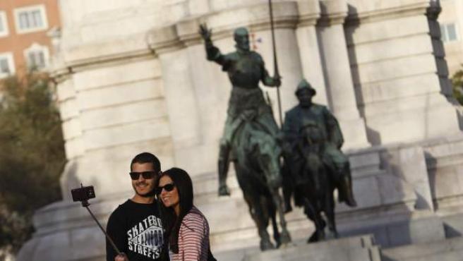 Unos turistas se fotografían en el Monumento a Miguel de Cervantes en la Plaza de España de Madrid.