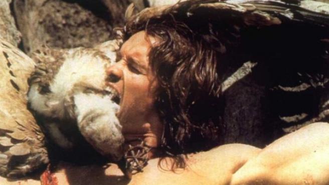 Escena de la película 'Conan, el Bárbaro', en el que el protagonista, interpretado por Arnold Schwarzenegger, muerde a un buitre.