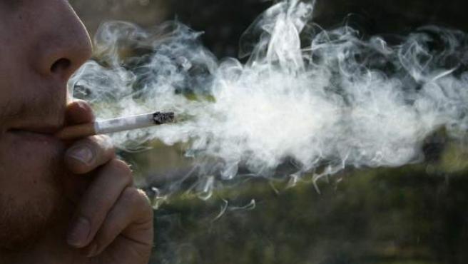 Un hombre fumando un cigarro.