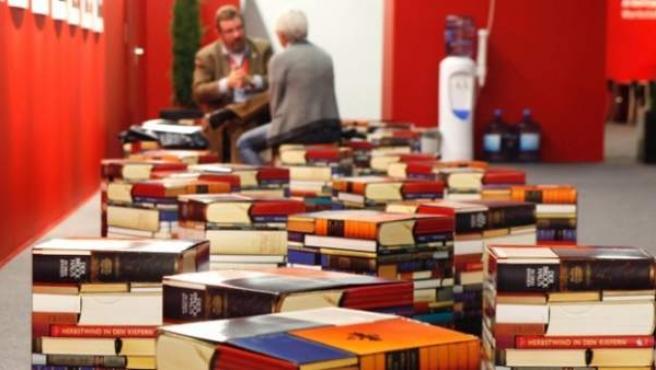 Dos hombres conversan tras varios lotes de libros.