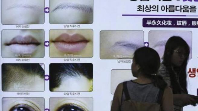 Una mujer mira un anuncio publicitario sobre una clínica de cirugía estética en Corea del Sur.