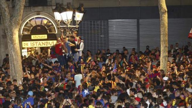 Aficionados del FC Barcelona celebran en la fuente de Canaletas la victoria de su equipo ante el Athletic de Bilbao, tras el partido de la final de la Copa del Rey de fútbol jugado en el Camp Nou, en el que el Barça se ha proclamado campeón por 1-3.