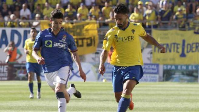 El delantero del Cádiz CF Kike Márquez (d) disputa un balón con el defensa del Real Oviedo Nacho López (i).