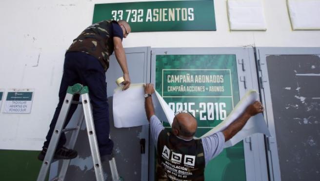 Operarios del Elche tapan la publicidad de la campaña de abonos para la siguiente temporada en el estadio Martínez Valero tras el descenso administrativo del club ilicitano a Segunda.