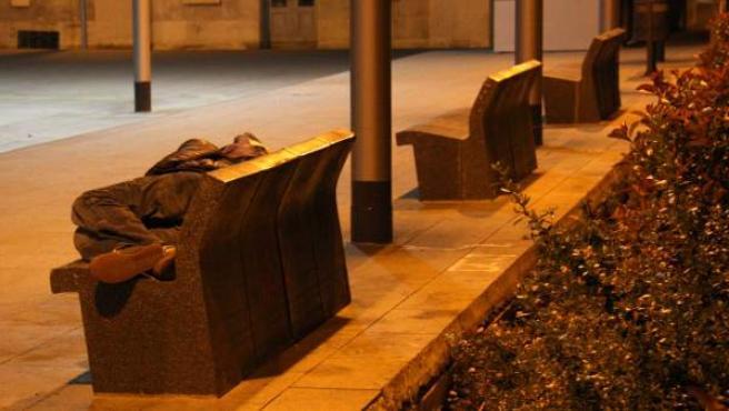 Un indigente pasa la noche en un banco de Barcelona.