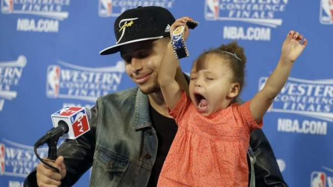 El base de los Golden State Warriors, Stephen Curry, junto a su hija Riley en rueda de prensa.