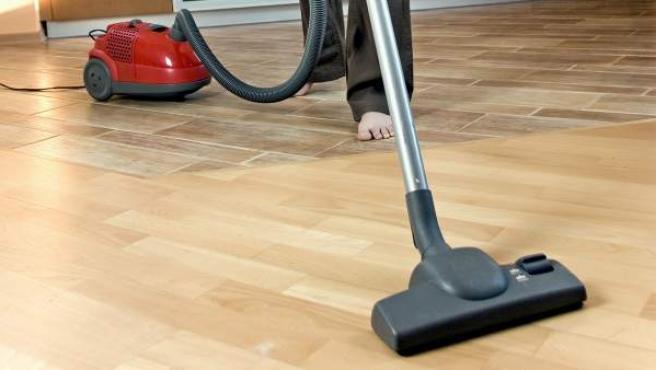 Una mujer limpia su casa con un aspirador.