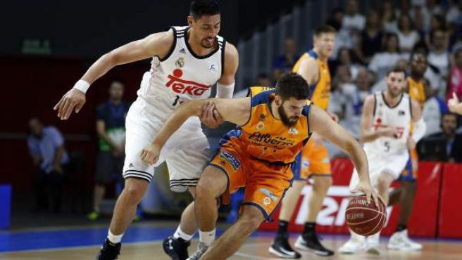 El alero del Real Madrid Gustavo Ayón (i) presiona al pívot del Valencia Basket Bojan Dubljevic