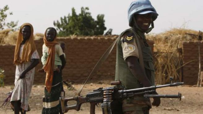 Dos refugiadas sudanesas caminan junto a un 'casco azul' de la ONU en el campo de Zamzam