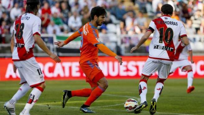 El centrocampista portugués del Valencia André Gomes (c) entre el defensa portugués Zé Castro (i) y el centrocampista Roberto Trashorras (d), del Rayo Vallecano,