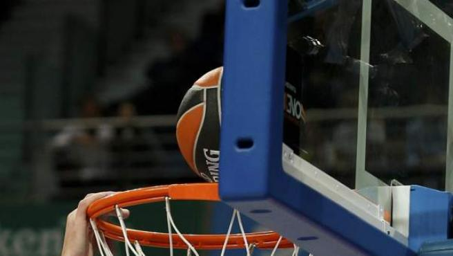 Un balón de baloncesto, en el momento de entrar en la canasta.