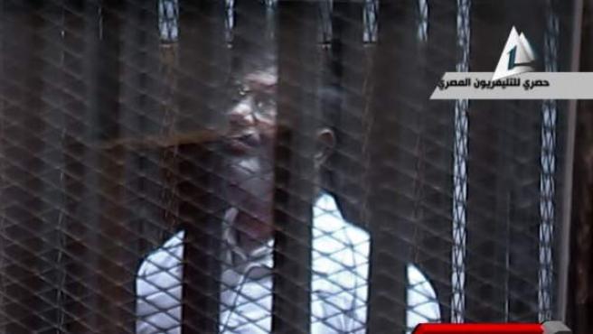 El expresidente egipcio, Muhamed Morsi, en la celda del juzgado donde se celebra el proceso contra él.
